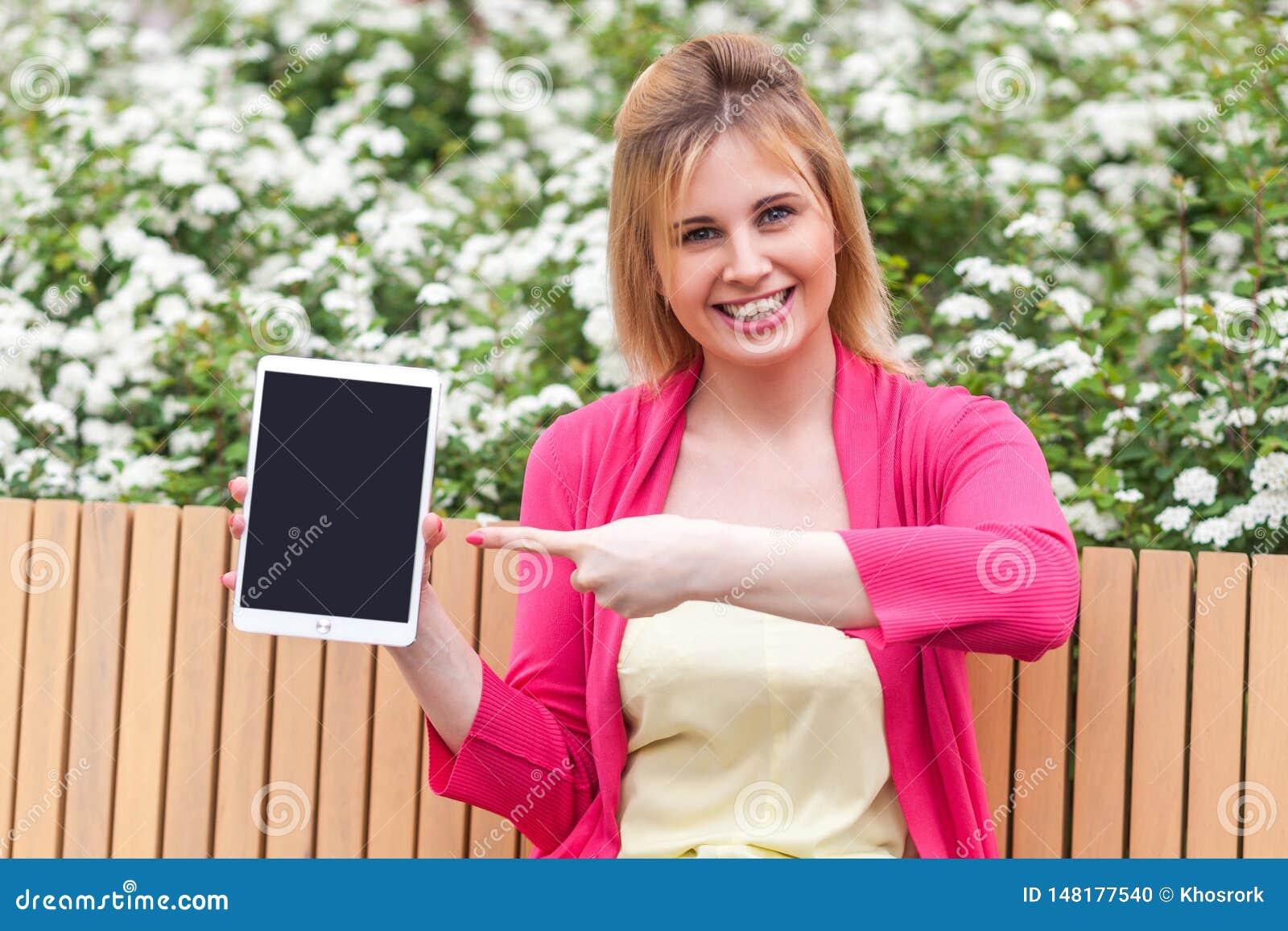 Młody bizneswoman w elegancja stylu obsiadaniu w ławce na parku mienie pastylki pusty ekran i wskazywać przyrząd z palec,