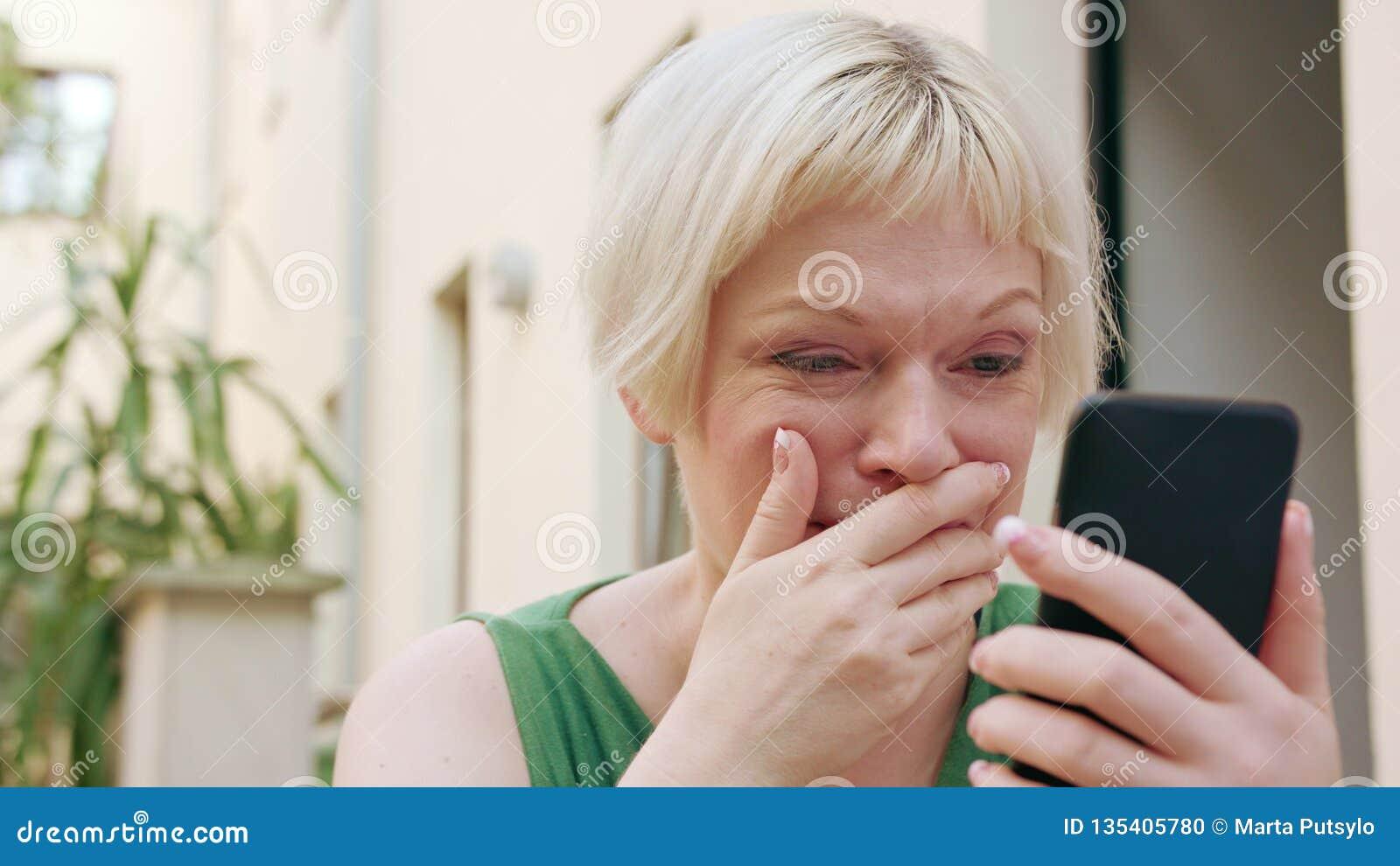 Młody blondynki kobiety obsiadanie Outside i Używa telefon