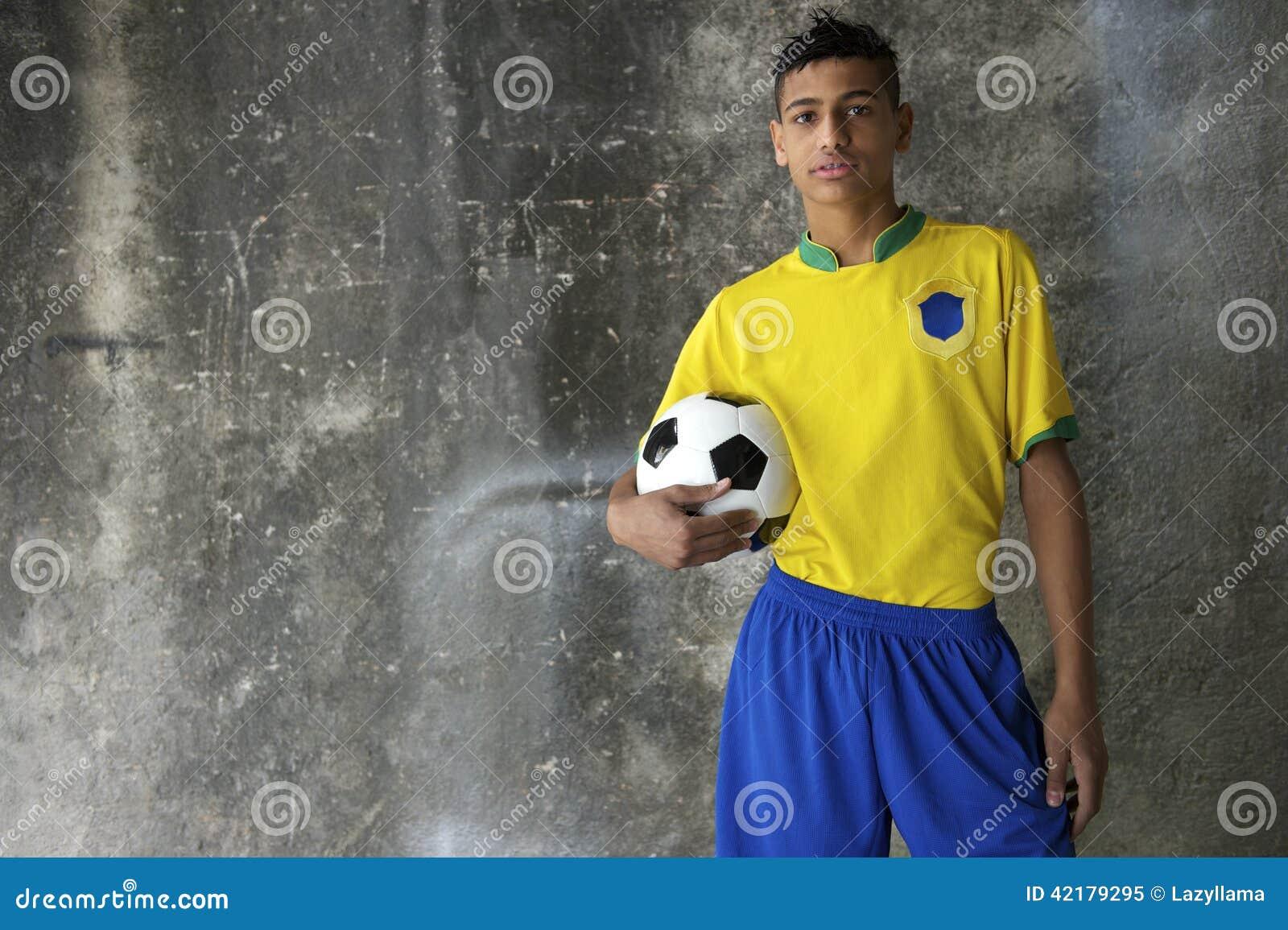 Młody Brazylijski futbolista w zestawu mienia futbolu
