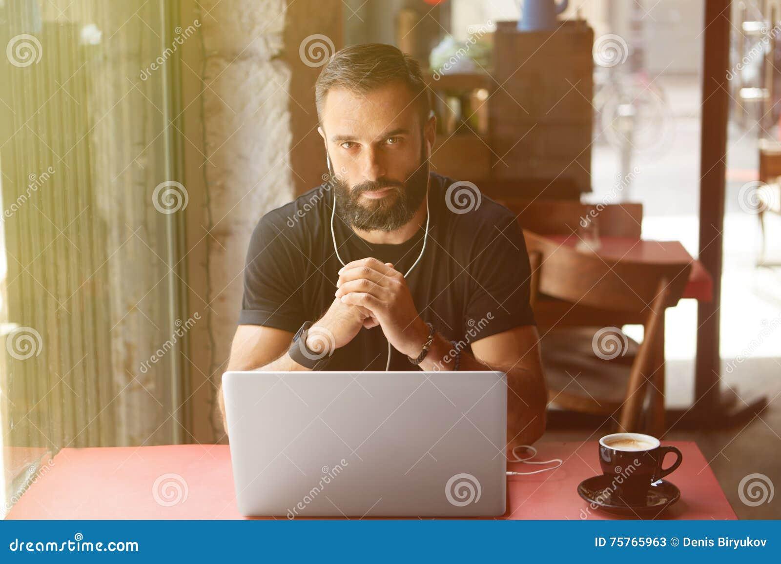 Młody Brodaty biznesmen Jest ubranym Czarnego Tshirt Pracującego laptopu Miastowej kawiarni Mężczyzna drewna stołu filiżanki kawy