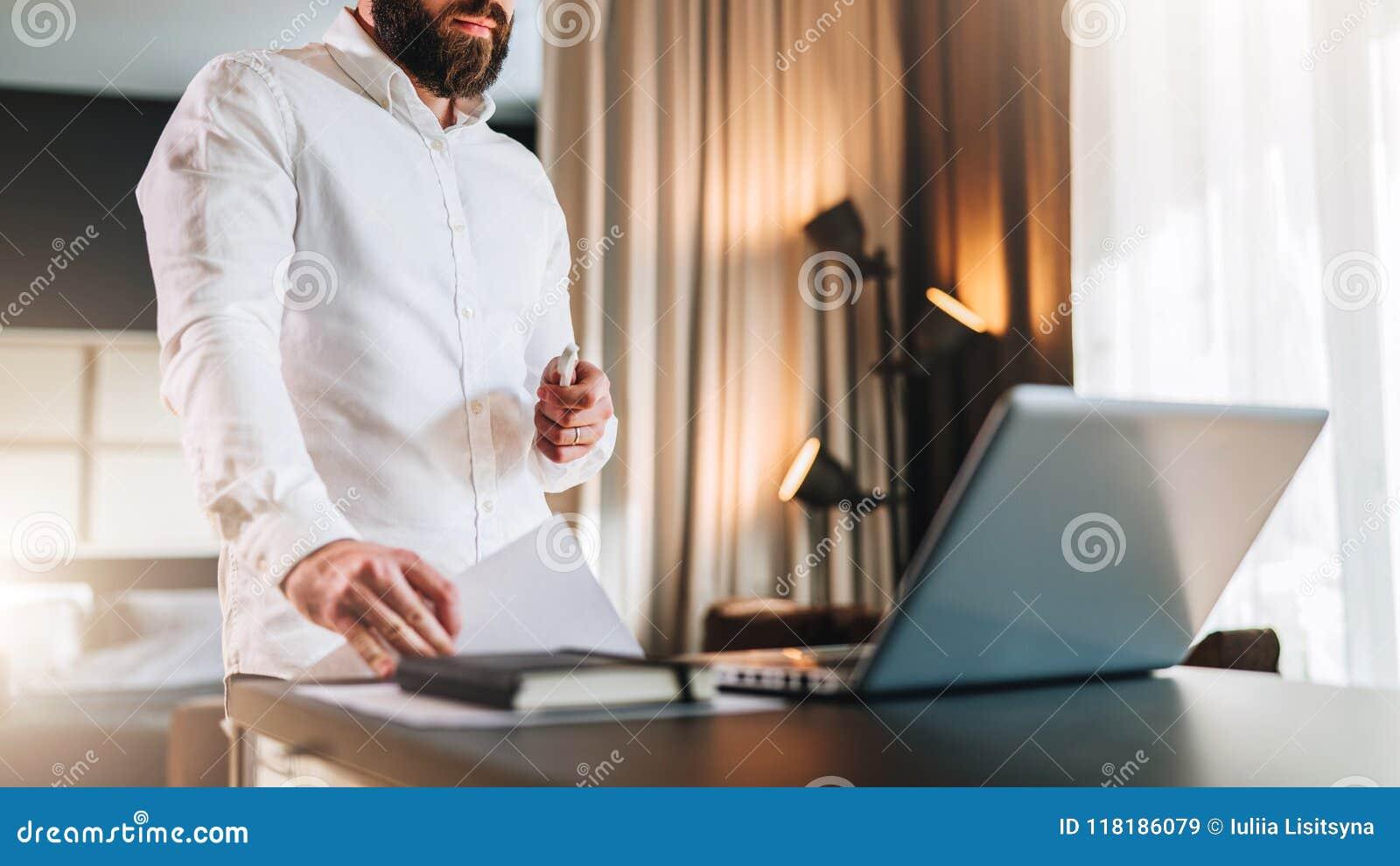 Młody brodaty biznesmen w białej koszula jest trwanie pobliskim biurkiem przed laptopem, mienie dokumenty Freelancer działanie