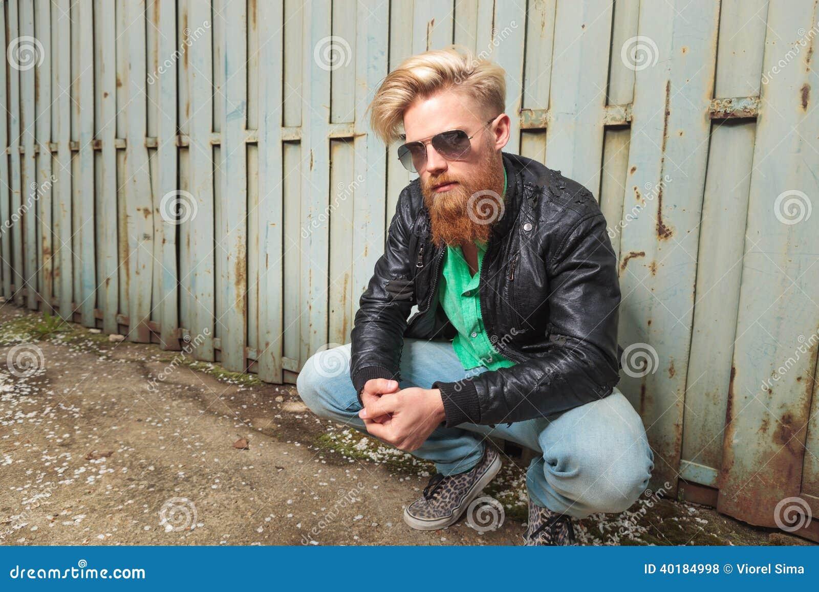 Młody brodaty mężczyzna kucać plenerowy