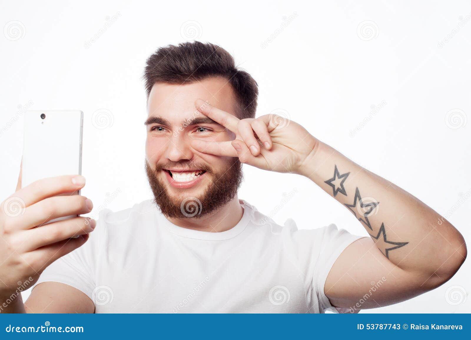 Młody brodaty mężczyzna z telefonem komórkowym