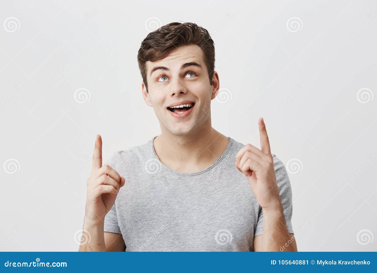 Młody caucasian facet jest ubranym szarą koszulkę wskazuje przy kopii przestrzenią up z forefingers patrzeje z szerokim uśmiechem