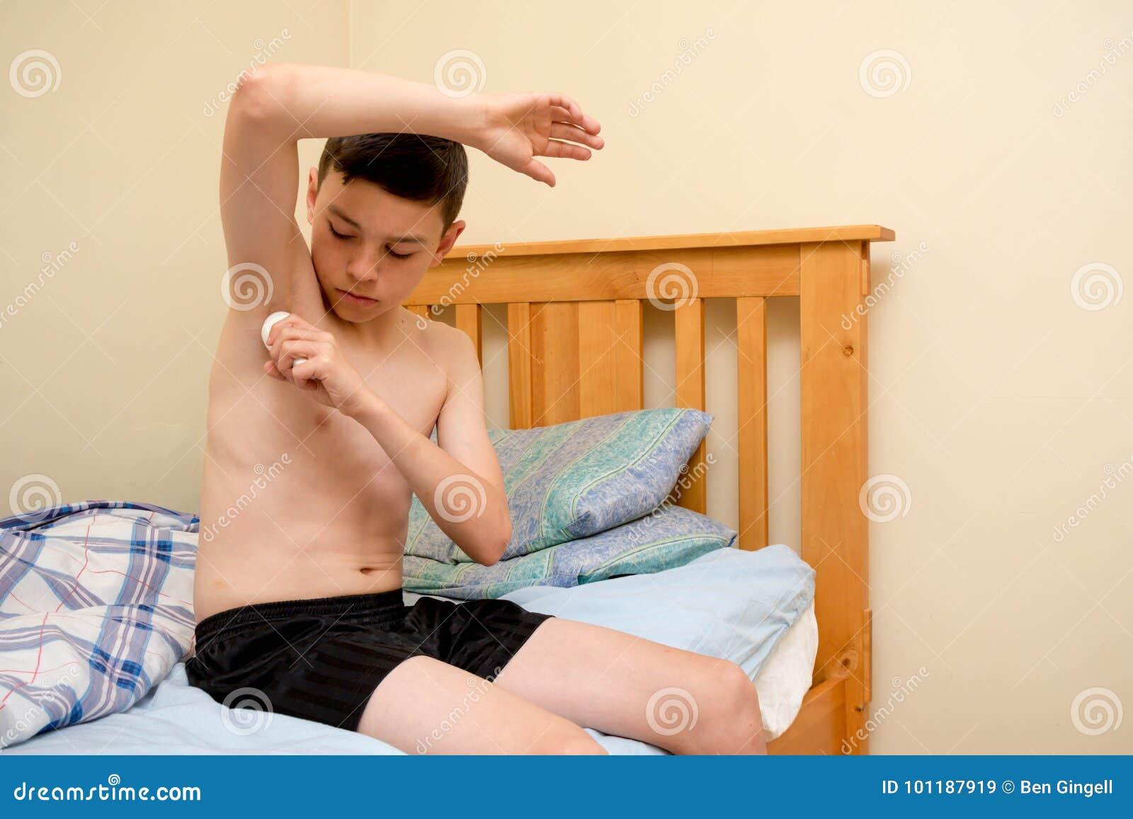 Młody caucasian nastoletni chłopak używa antiperspirant