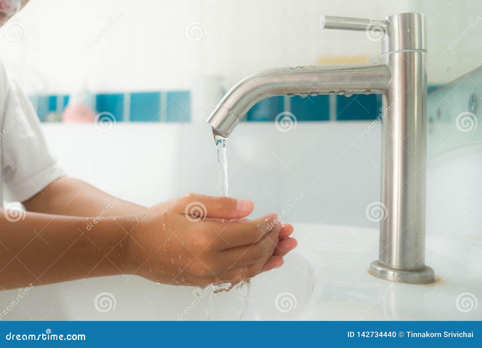 Młody chłopiec obmycie jego ręka wodą od faucet