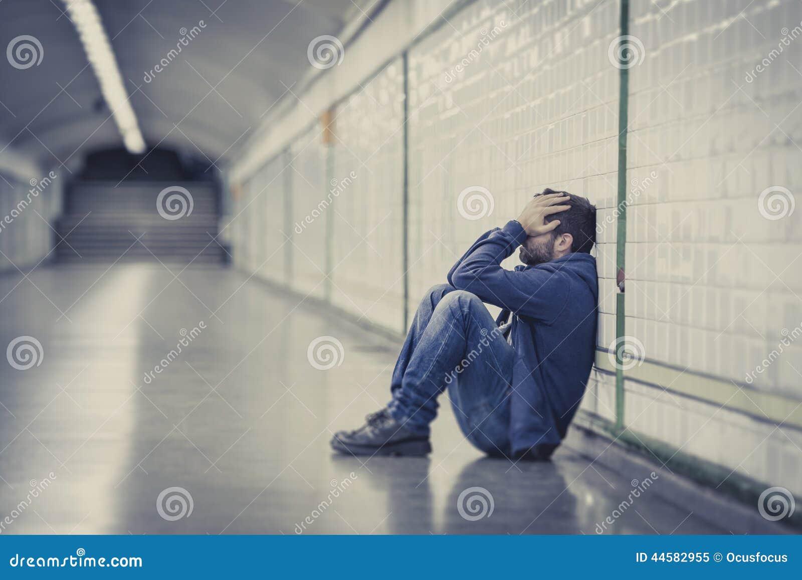 Młody chory mężczyzna gubił cierpienie depresji obsiadanie na zmielonym ulicznym metro tunelu