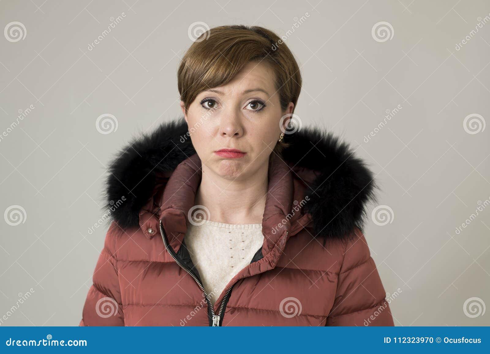 Młody cukierki i smutna czerwona włosiana kobieta pozuje patrzeć kamera jest ubranym ciepłą zima żakieta kurtkę z kapiszonem mark