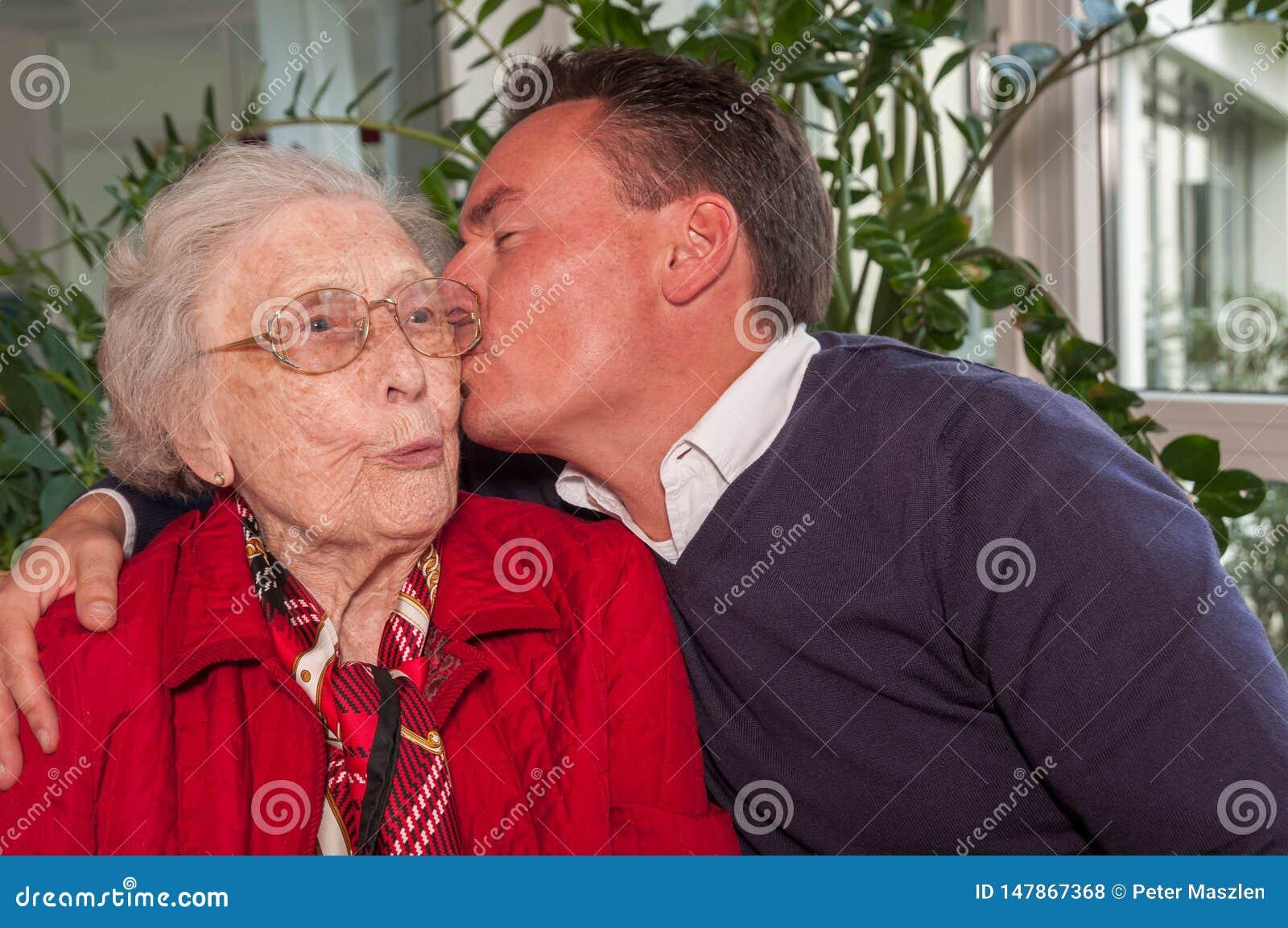 Młody człowiek całuje jego babci