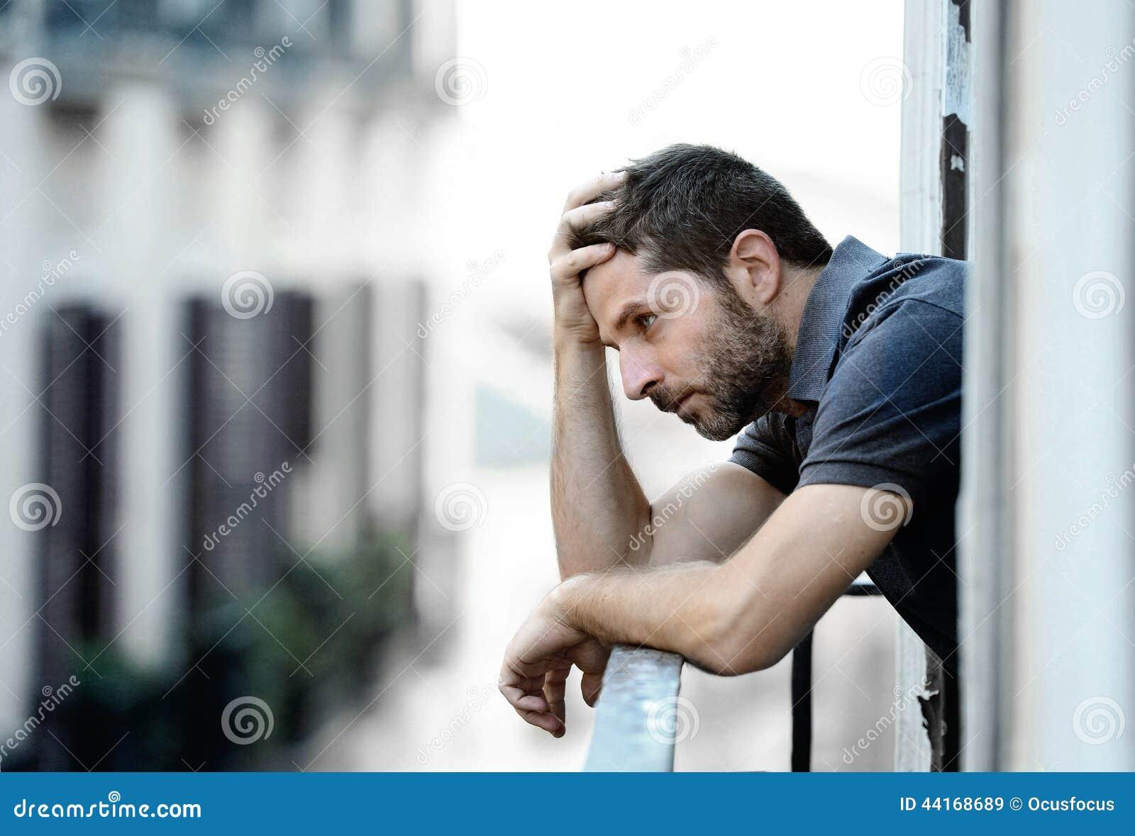 Młody człowiek cierpi emocjonalnego kryzys i żal przy balkonem w depresji