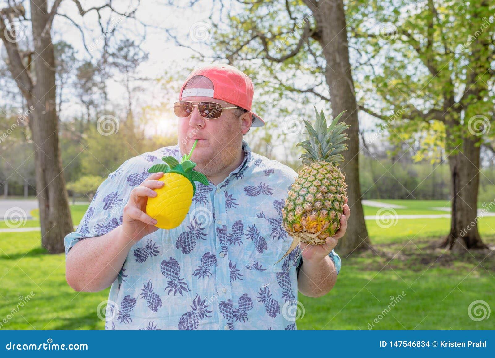 Młody człowiek cieszy się ananasowego napój