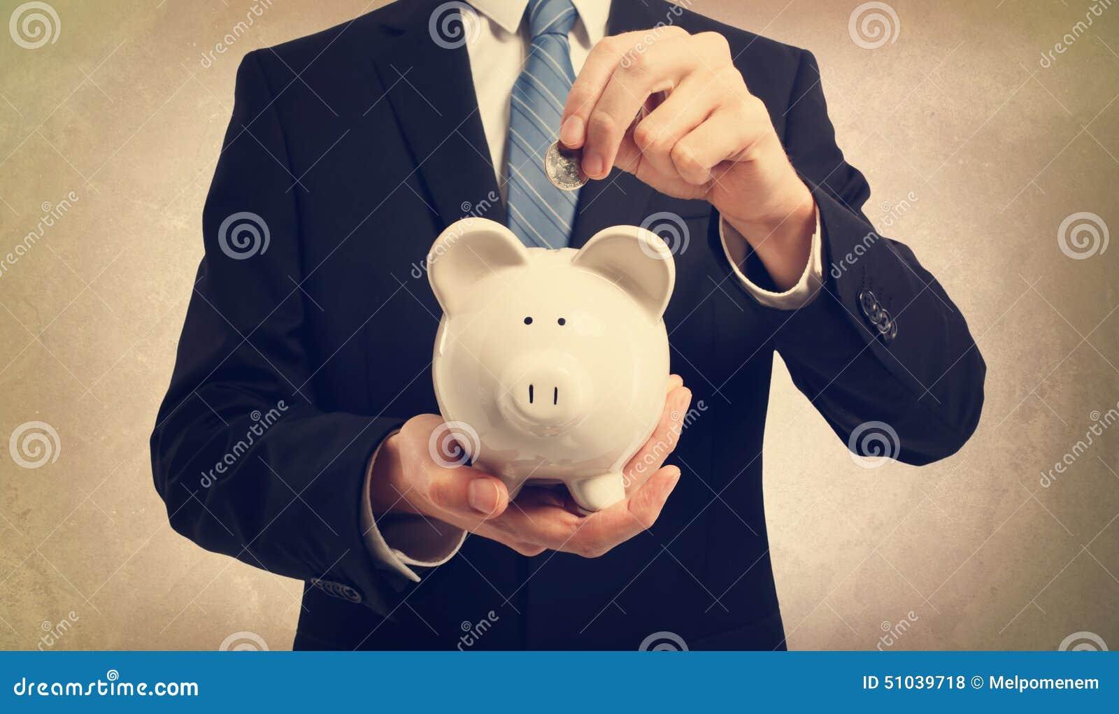 Młody człowiek deponuje pieniądze w prosiątko banku