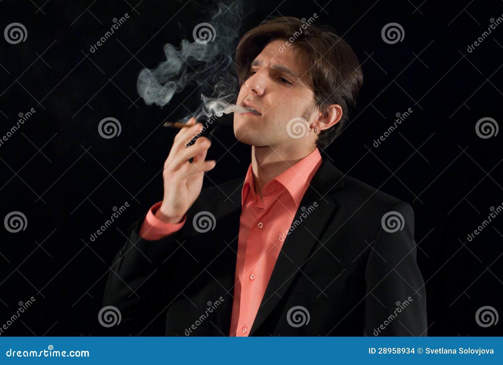 Młody człowiek dymi cygaro