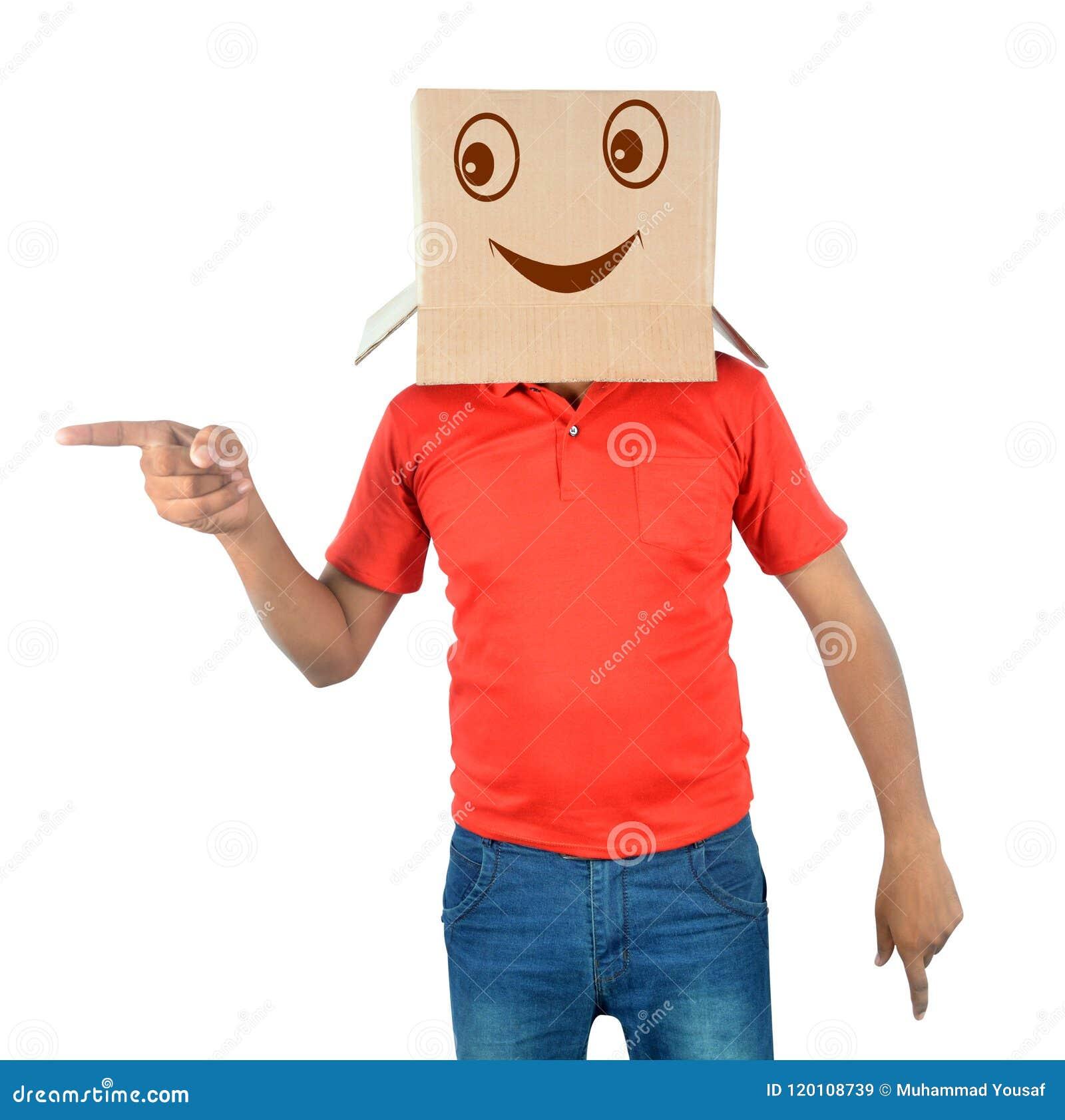 Młody człowiek gestykuluje z kartonem na jego głowie z smiley