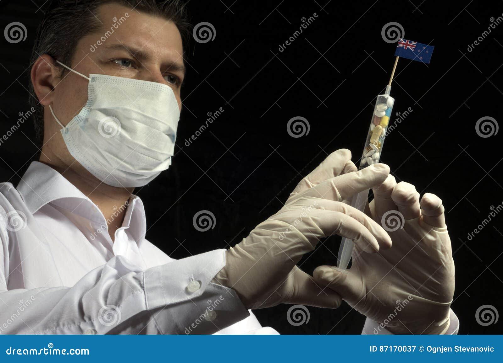 Młody człowiek jako lekarka daje medycznemu zastrzykowi Nowa Zelandia f