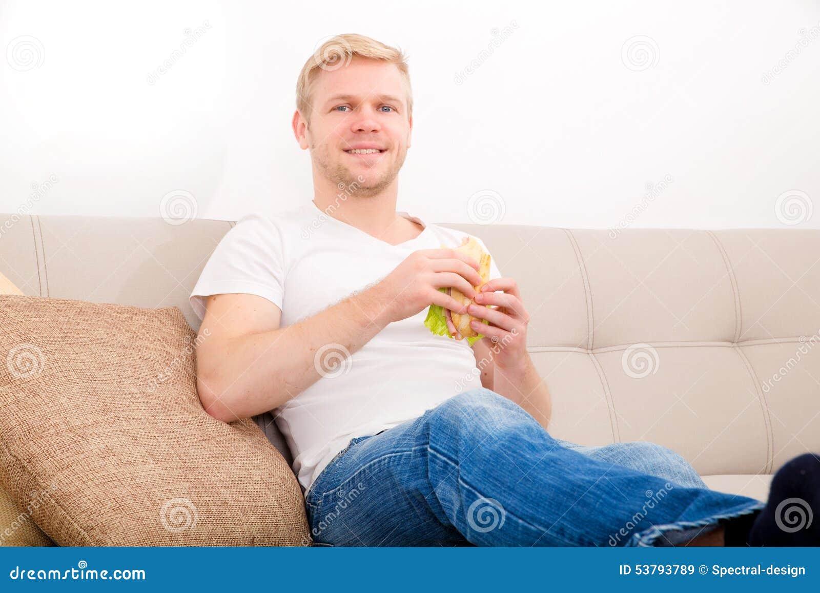 Młody człowiek je kanapkę w domu