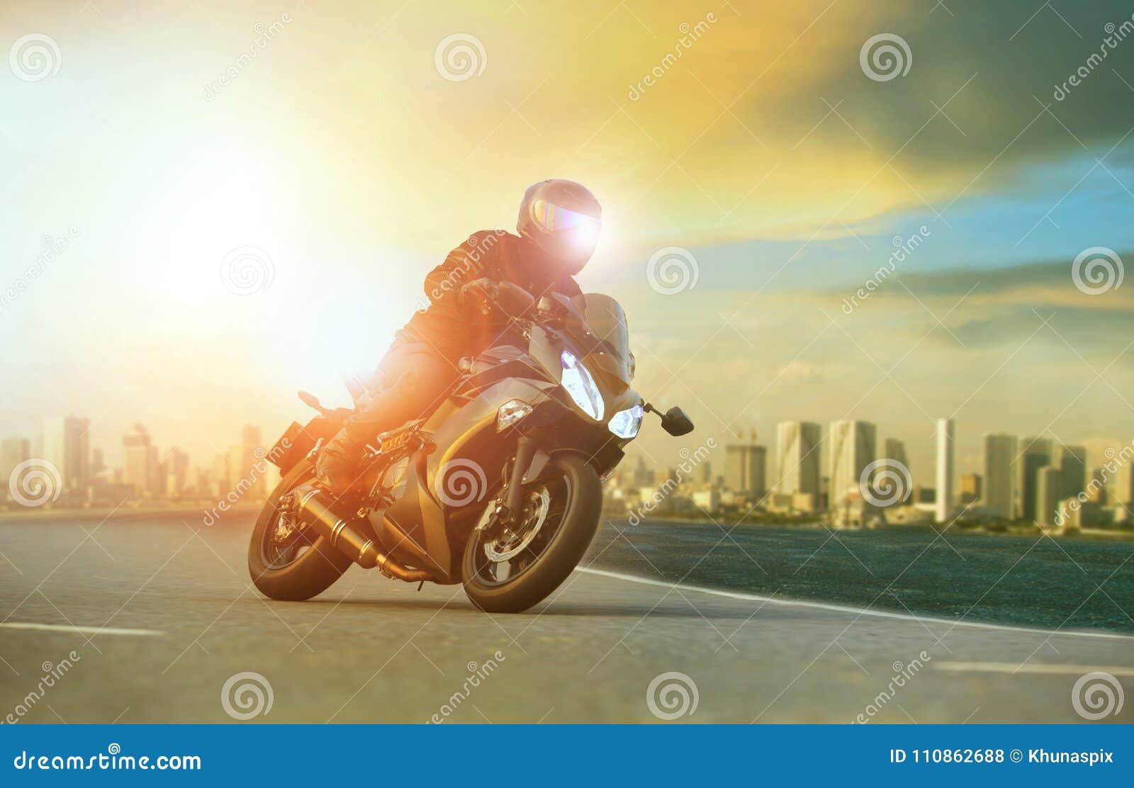 Młody człowiek jedzie dużego motocykl opiera na ostrze krzywie z urba