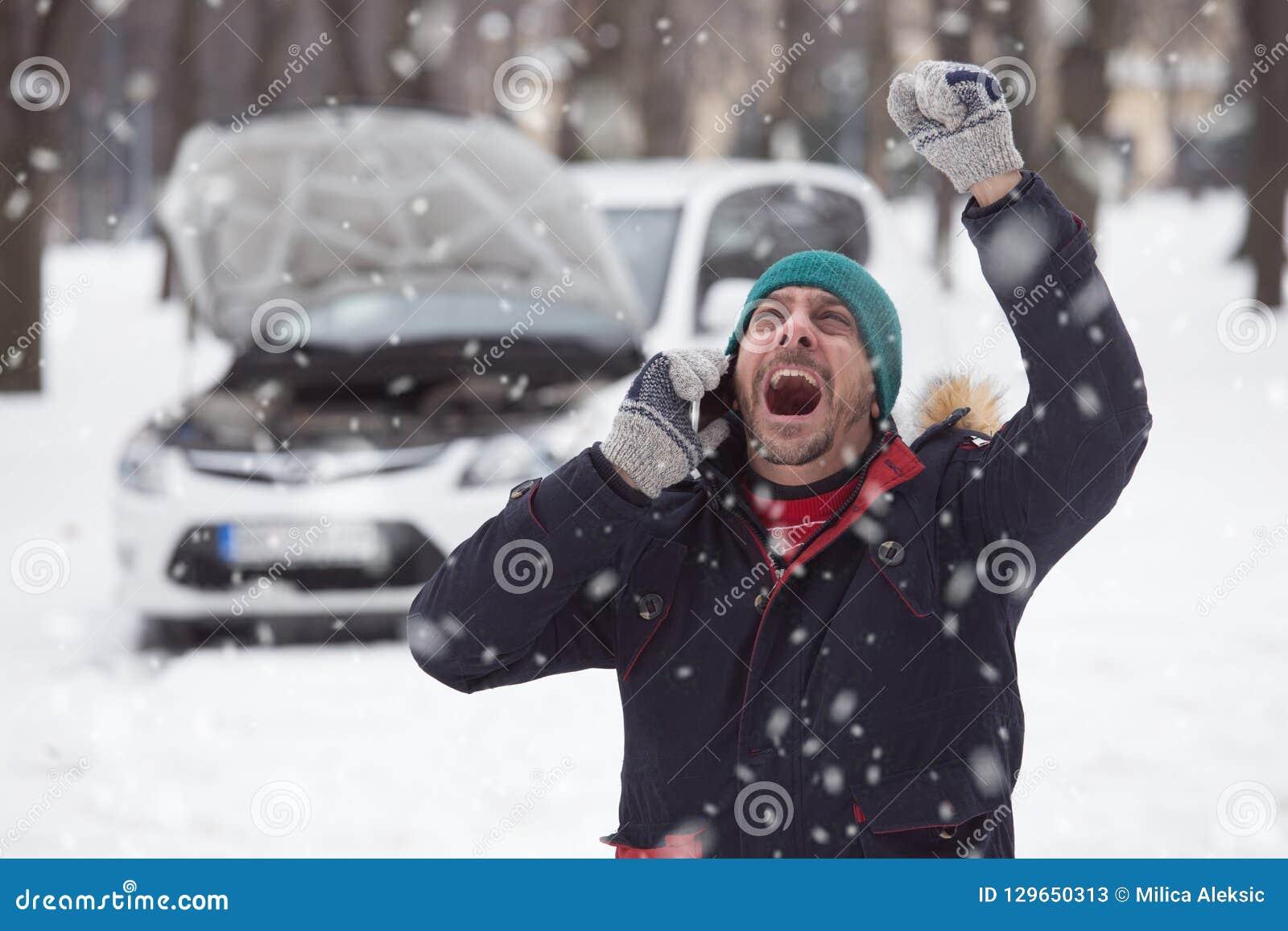 Młody człowiek jest pod stresem ponieważ jego psujący się samochód na śniegu da