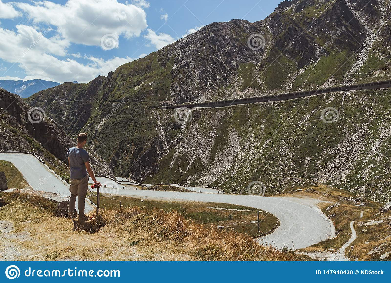 Młody człowiek kontempluje curvy drogowy pochodzić w dolinie z longboard