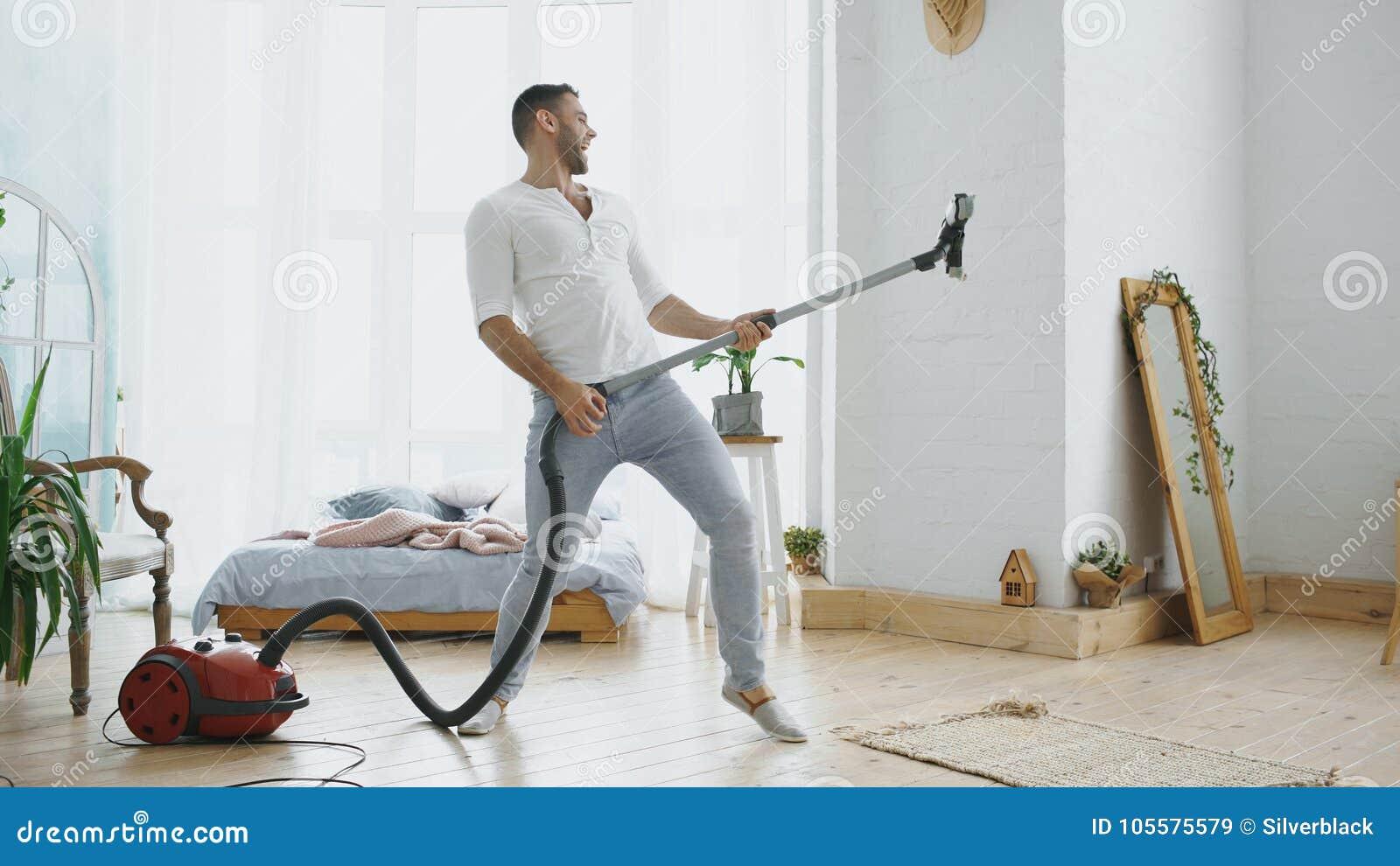 Młody człowiek ma zabawy cleaning dom z próżniowego cleaner tanem lubi gitarzysty