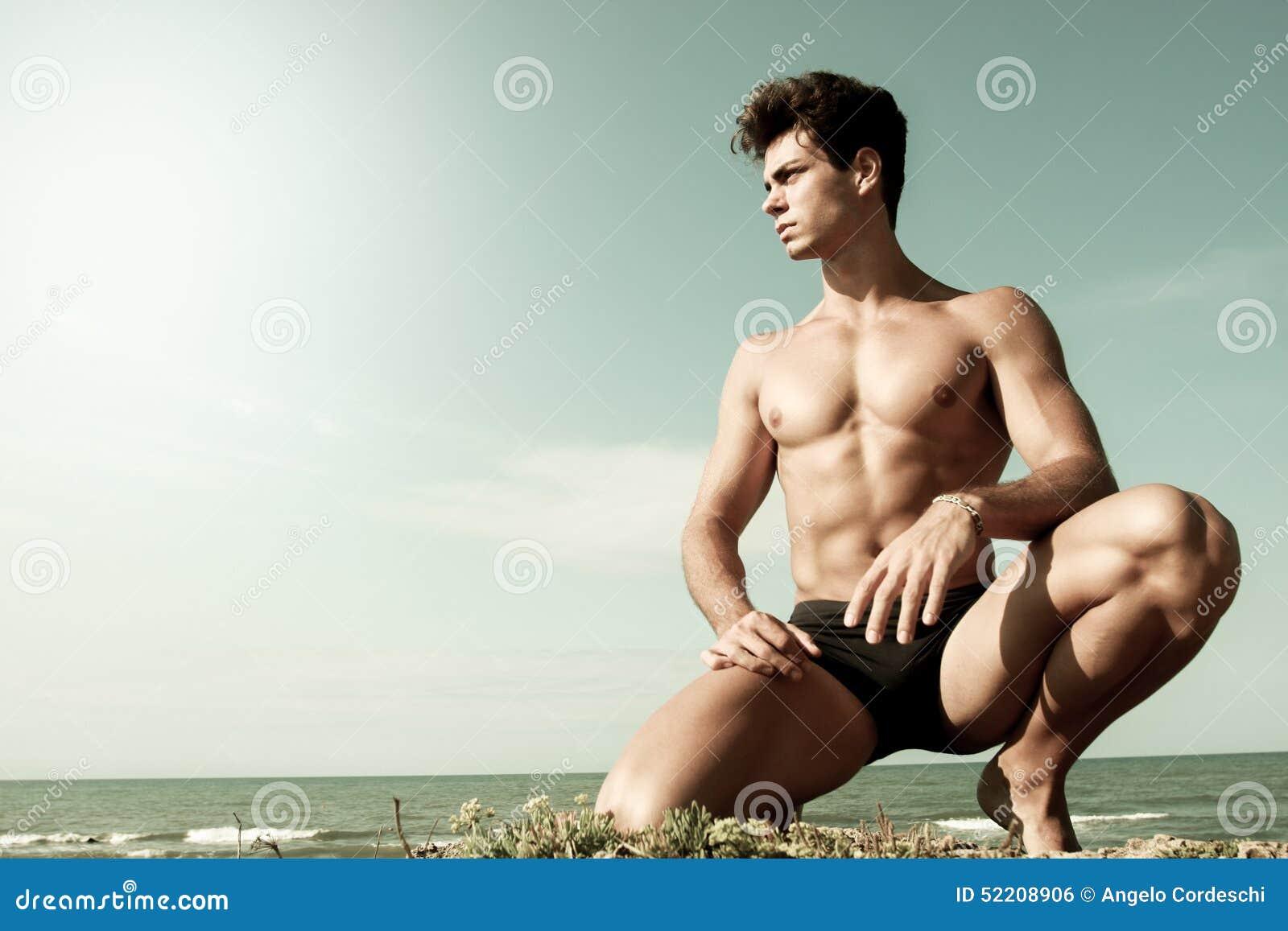 Młody człowiek nagi na jego kolanach Morze behind i niebo