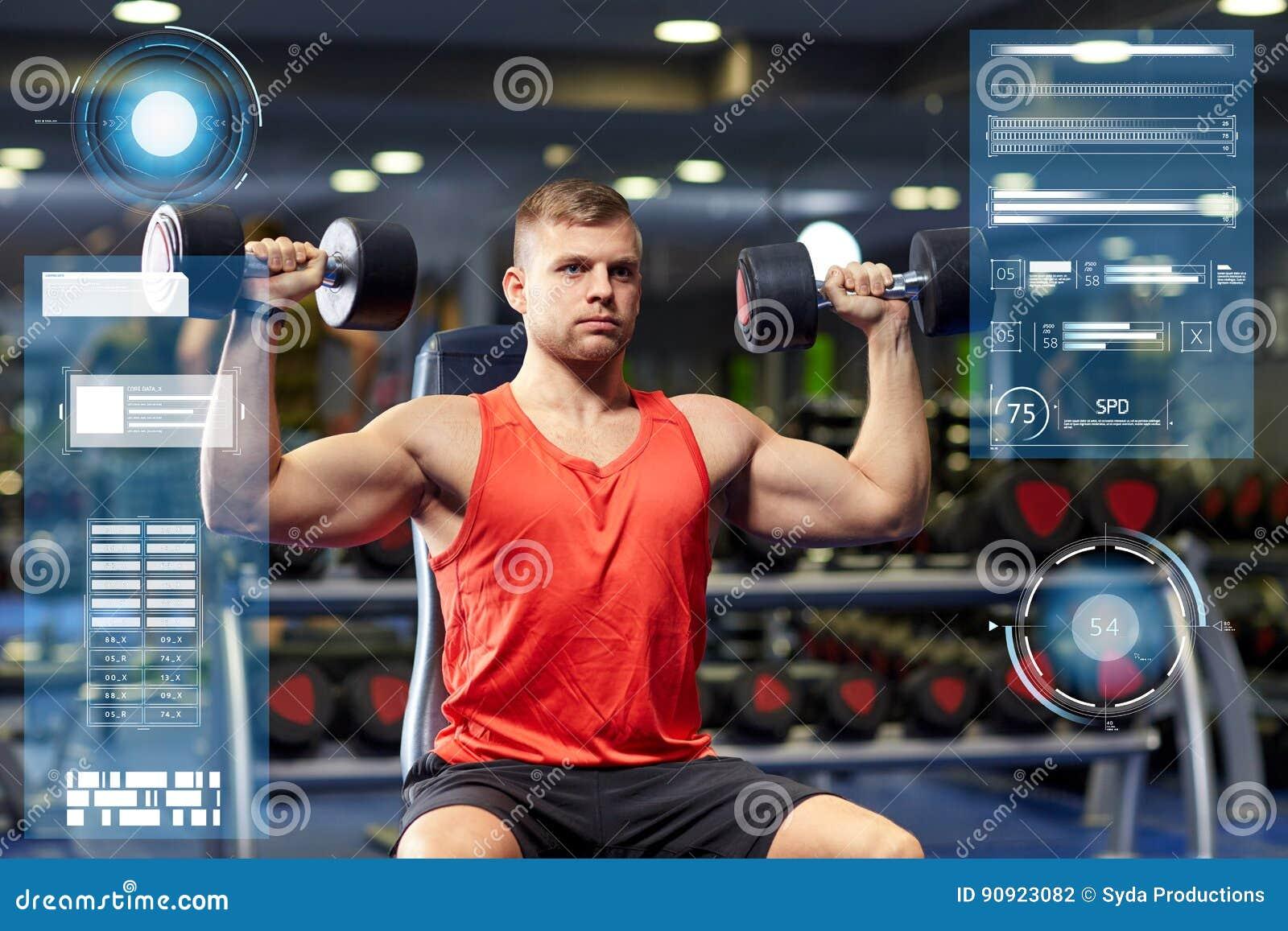 Młody człowiek napina mięśnie w gym z dumbbells