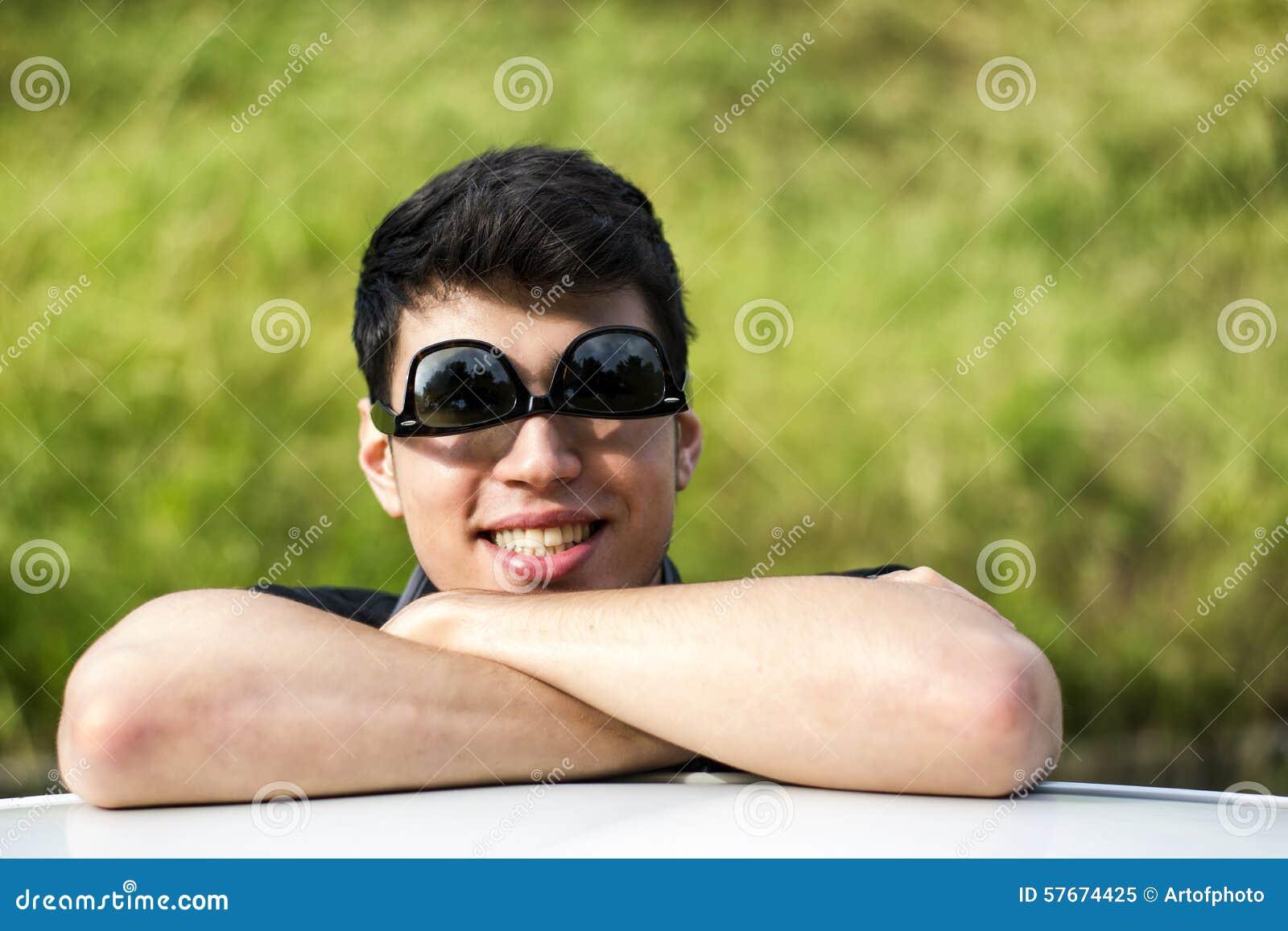 Młody człowiek patrzeje kamerę plenerową, opierający z