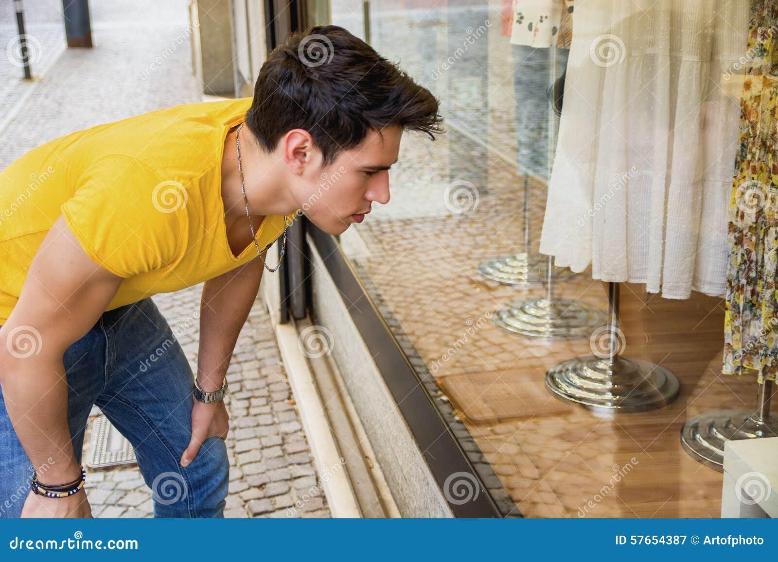Młody Człowiek Patrzeje mod rzeczy w Sklepowym okno
