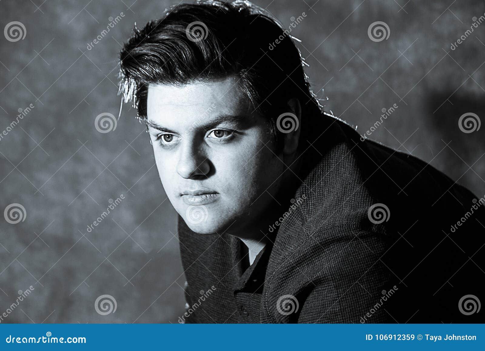 Młody człowiek patrzeje przestrzeń nad pracownianym tłem w czarny i biały