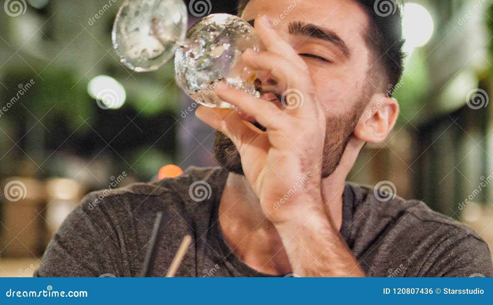 Młody człowiek pijący outside przy nocą