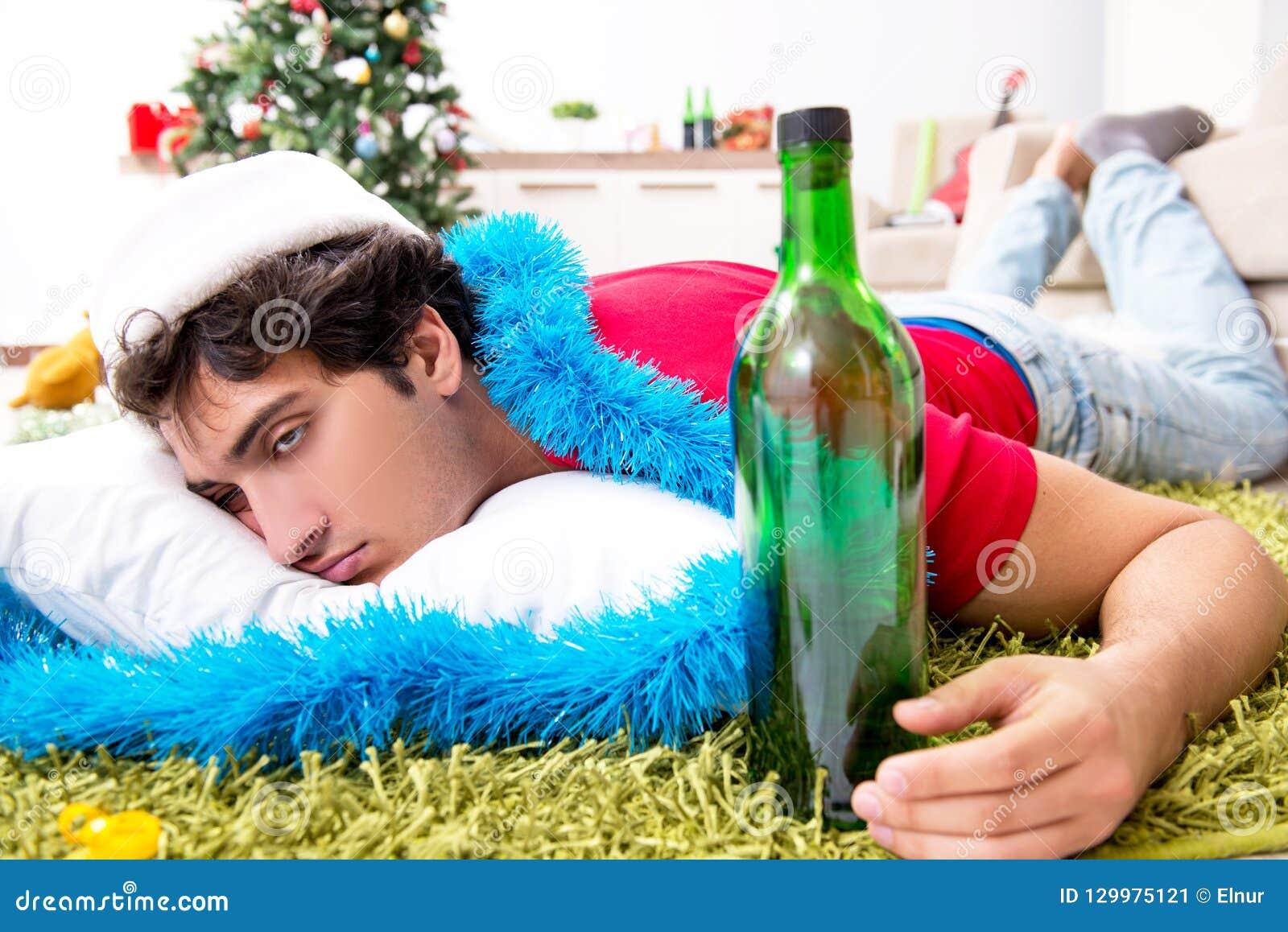 Młody człowiek pijący w domu po przyjęcia gwiazdkowego