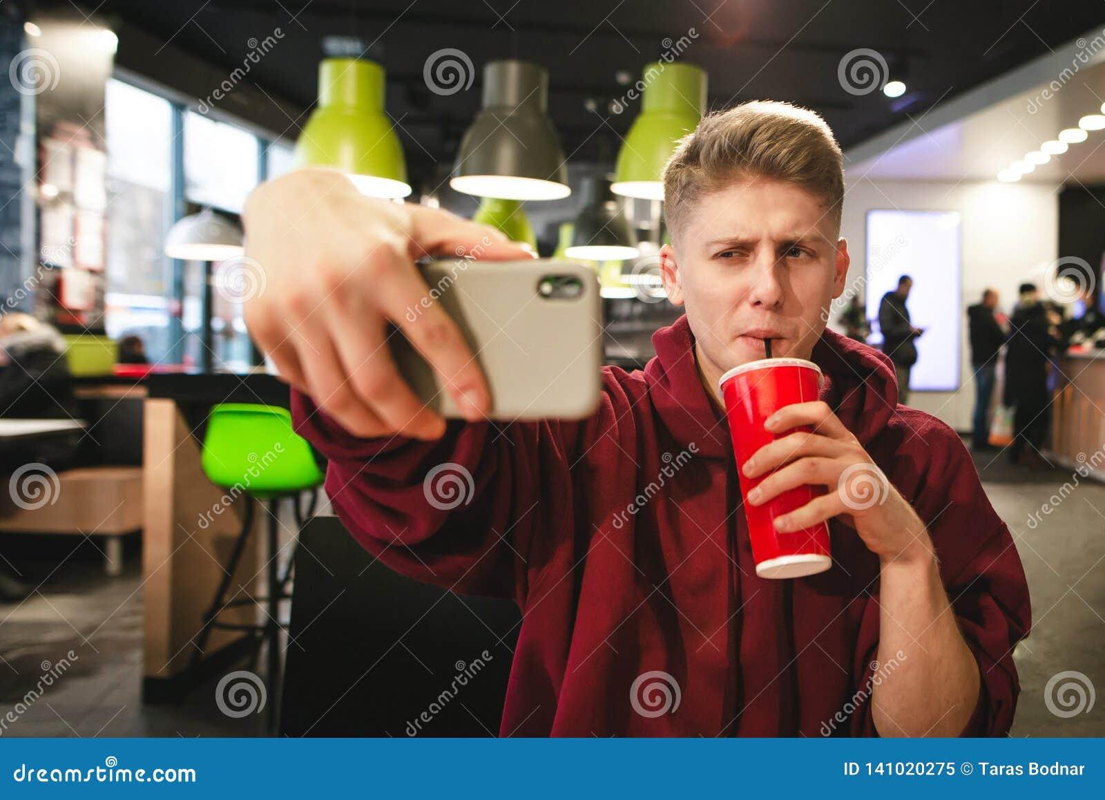 Młody człowiek pije napój od czerwonego szkła i robi selfie