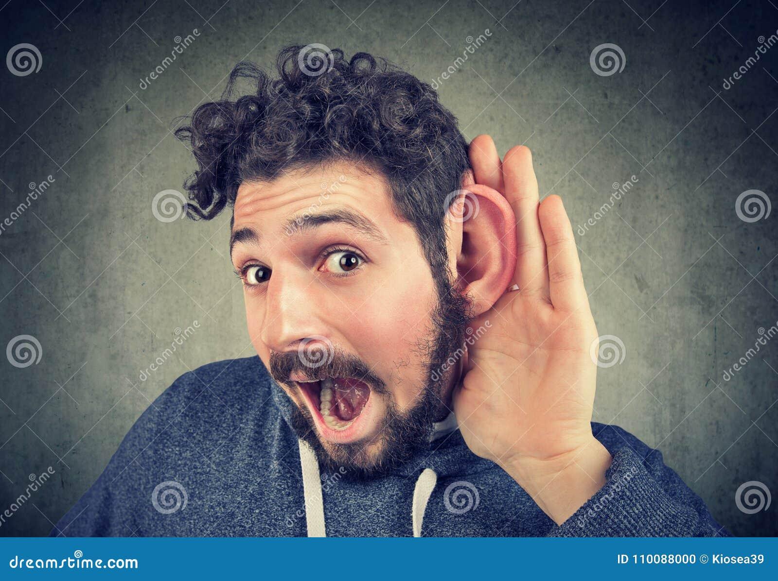 Młody człowiek próby słuchać ostrożnie
