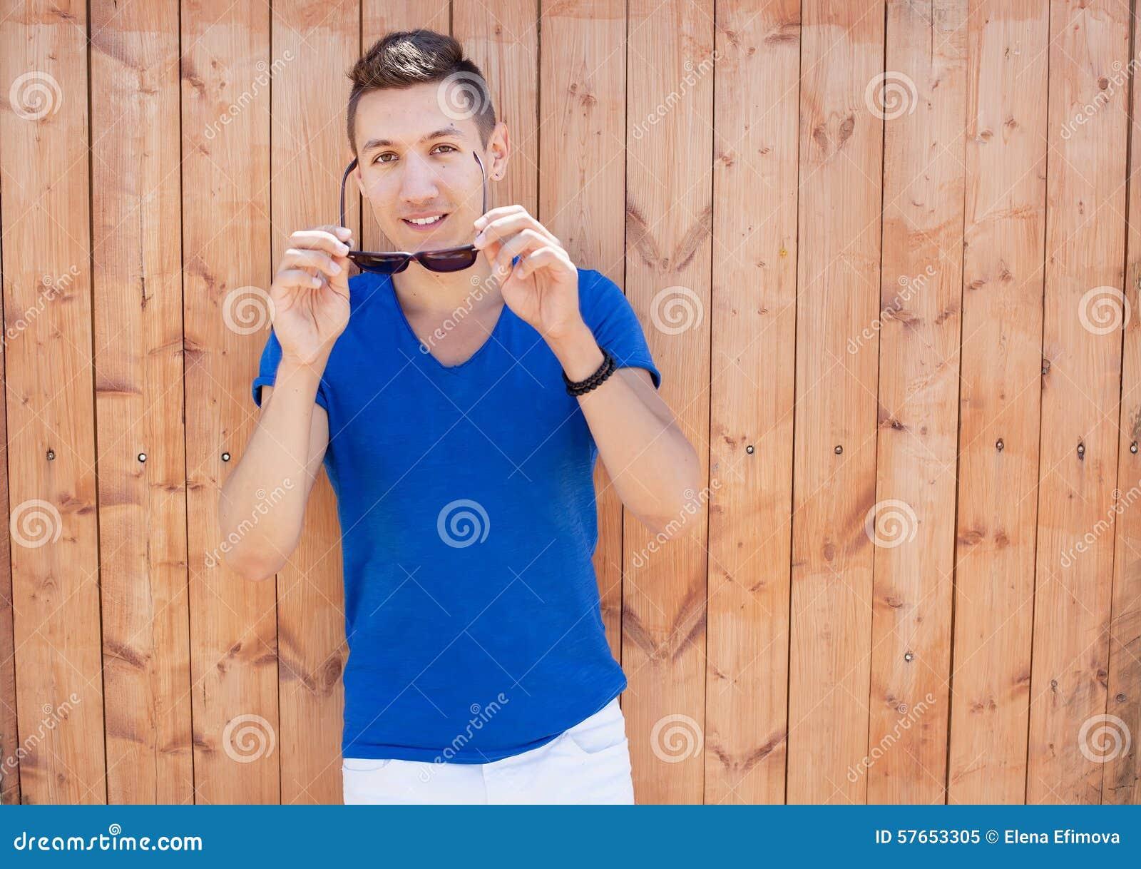 Młody człowiek przy drewnianą ścianą