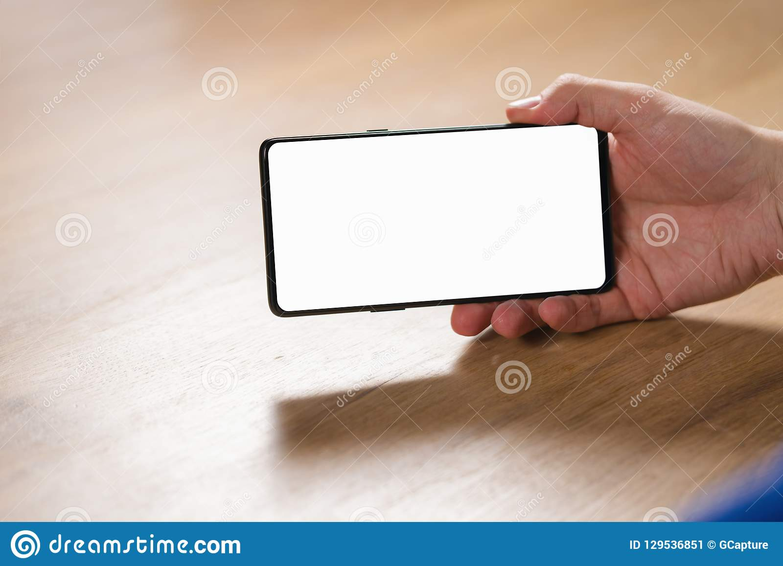Młody człowiek ręki mienia smartphone z pustym bielu ekranem w krajobrazowym trybie