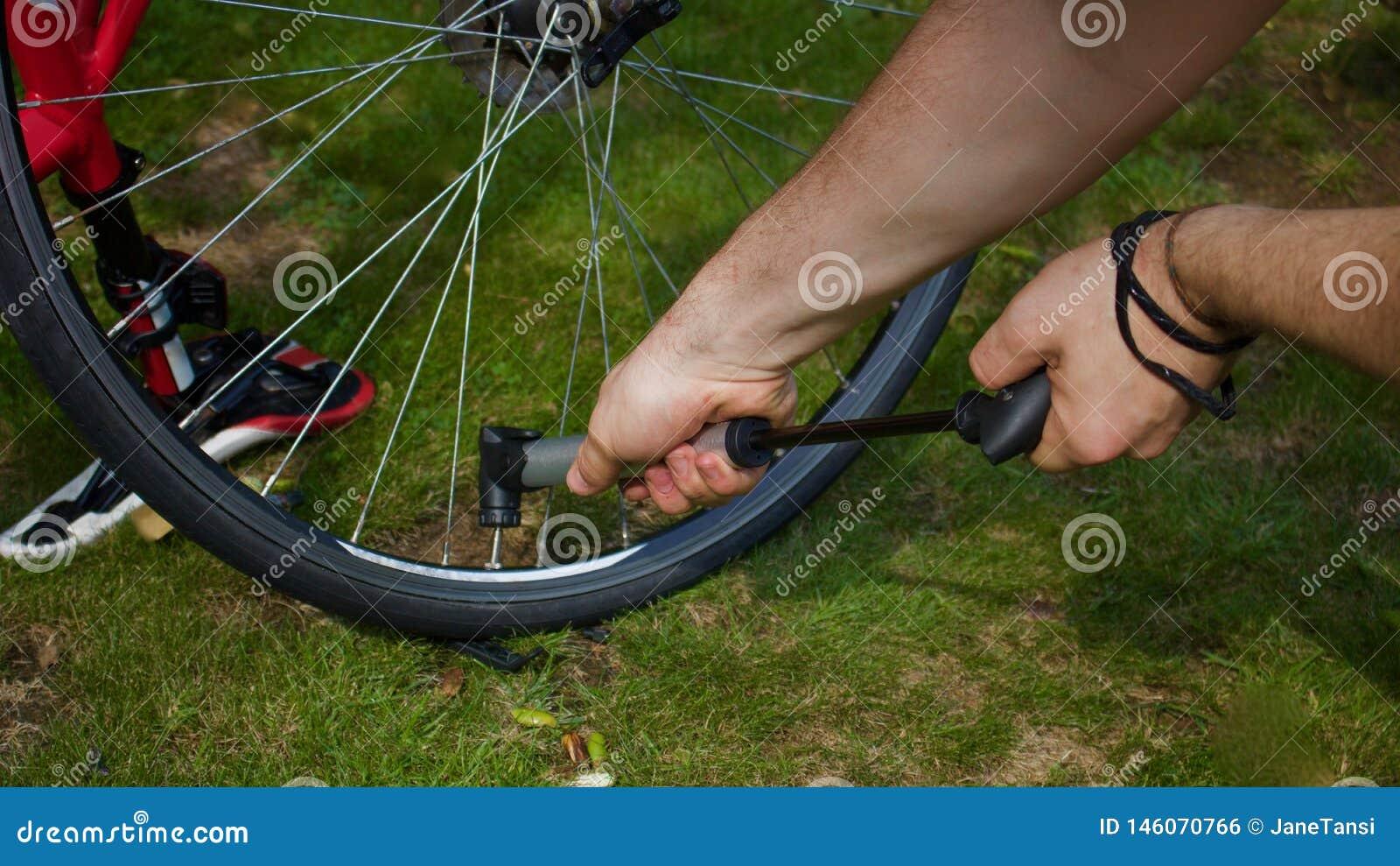 Młody człowiek ręki pompuje powietrze w rowerową oponę używać ręki pompę - wizerunek