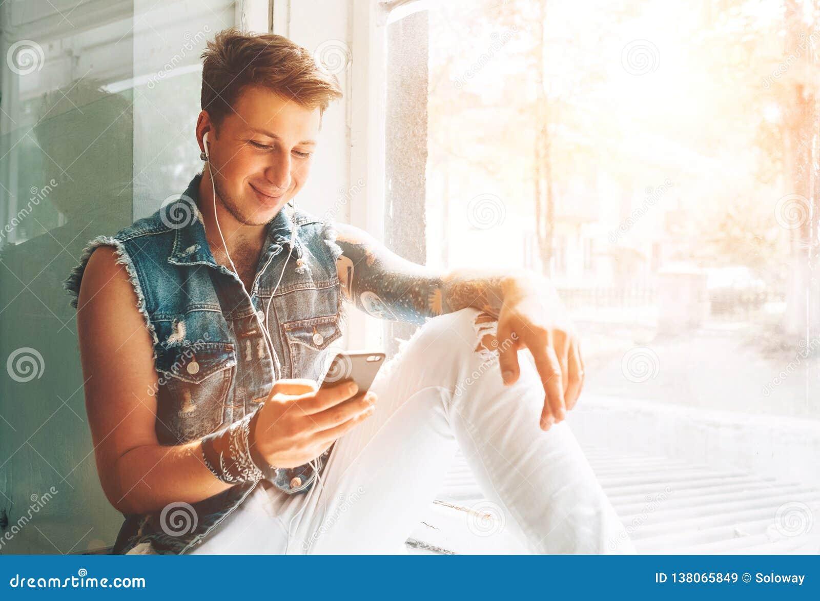 Młody człowiek słucha muzykę z hełmofonami i smartphone obsiadanie na windowsill