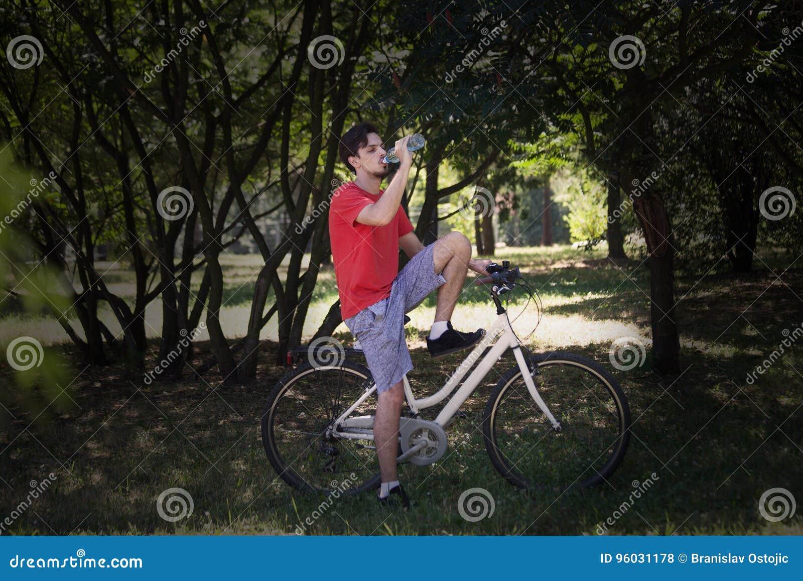 Młody człowiek siedzi na rowerze w drewnianej odpoczynkowej napój wodzie
