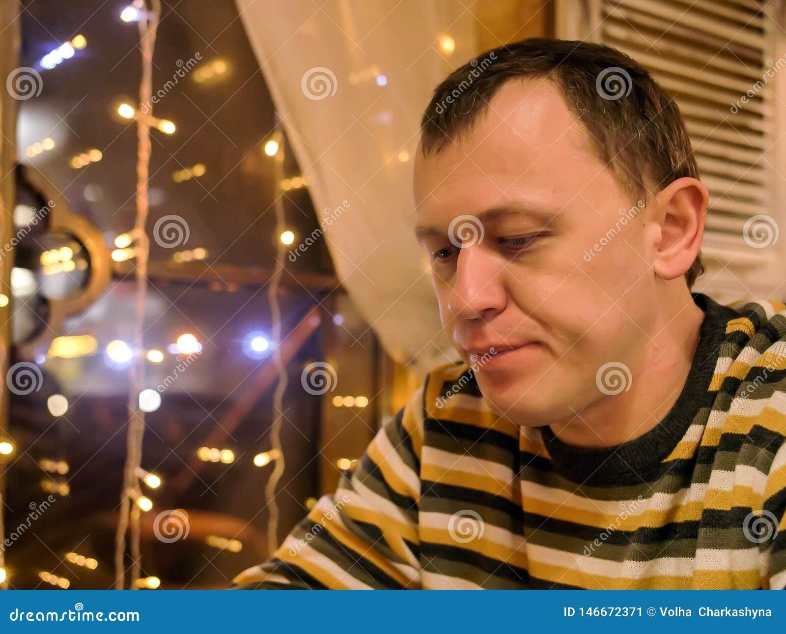 Młody człowiek siedzi w wieczór w kawiarni blisko okno