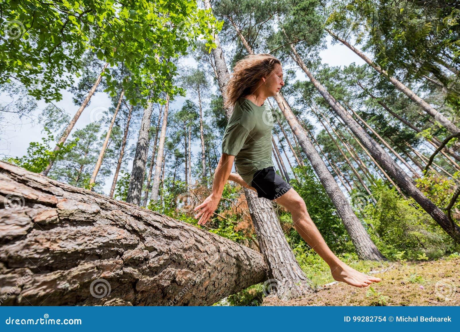 Młody człowiek skacze nad drzewnym bagażnikiem w lesie