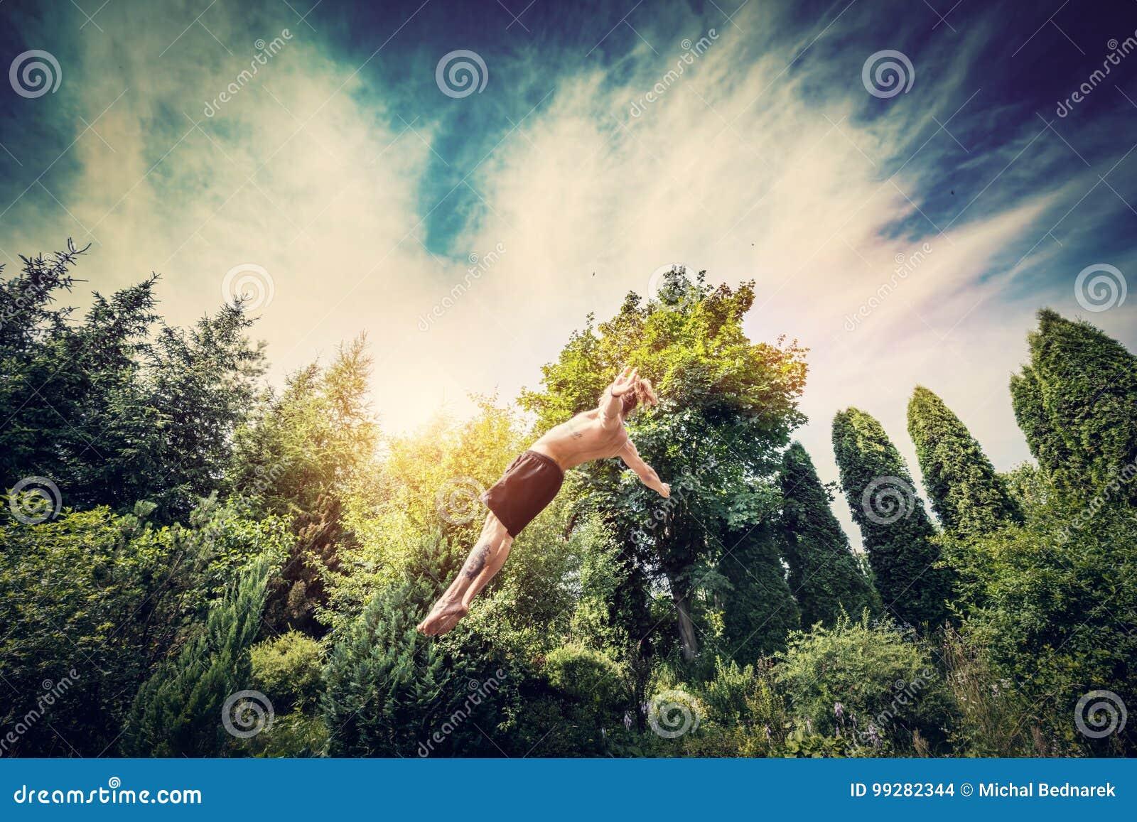 Młody człowiek skokowa wysokość w ogródzie