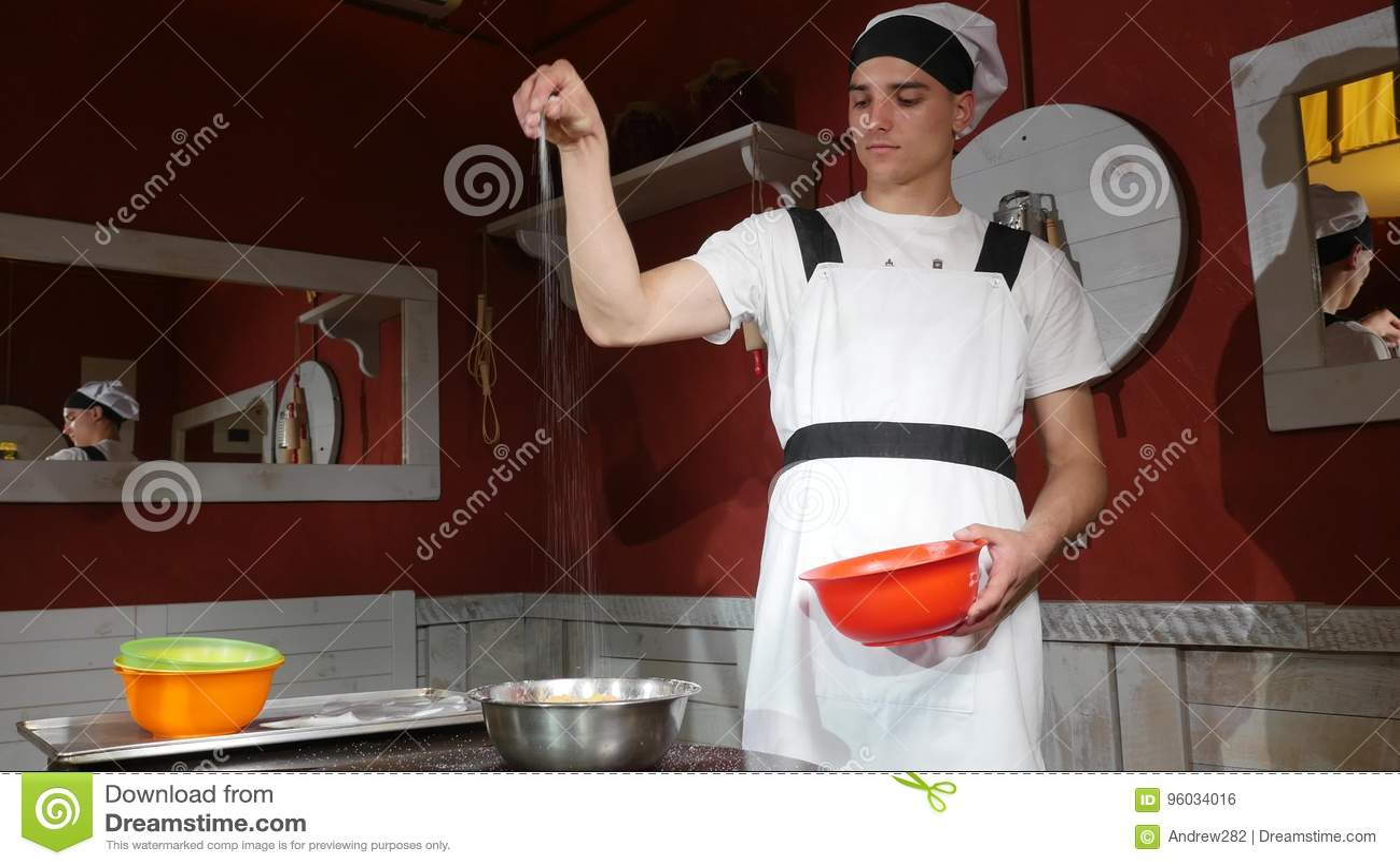 Młody człowiek spada cukier na talerzu morele na drewno stole