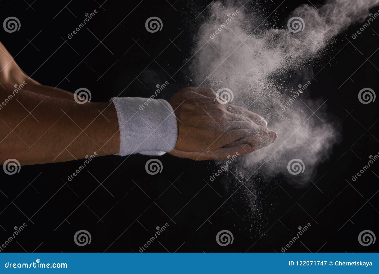 Młody człowiek stosuje kreda proszek na rękach
