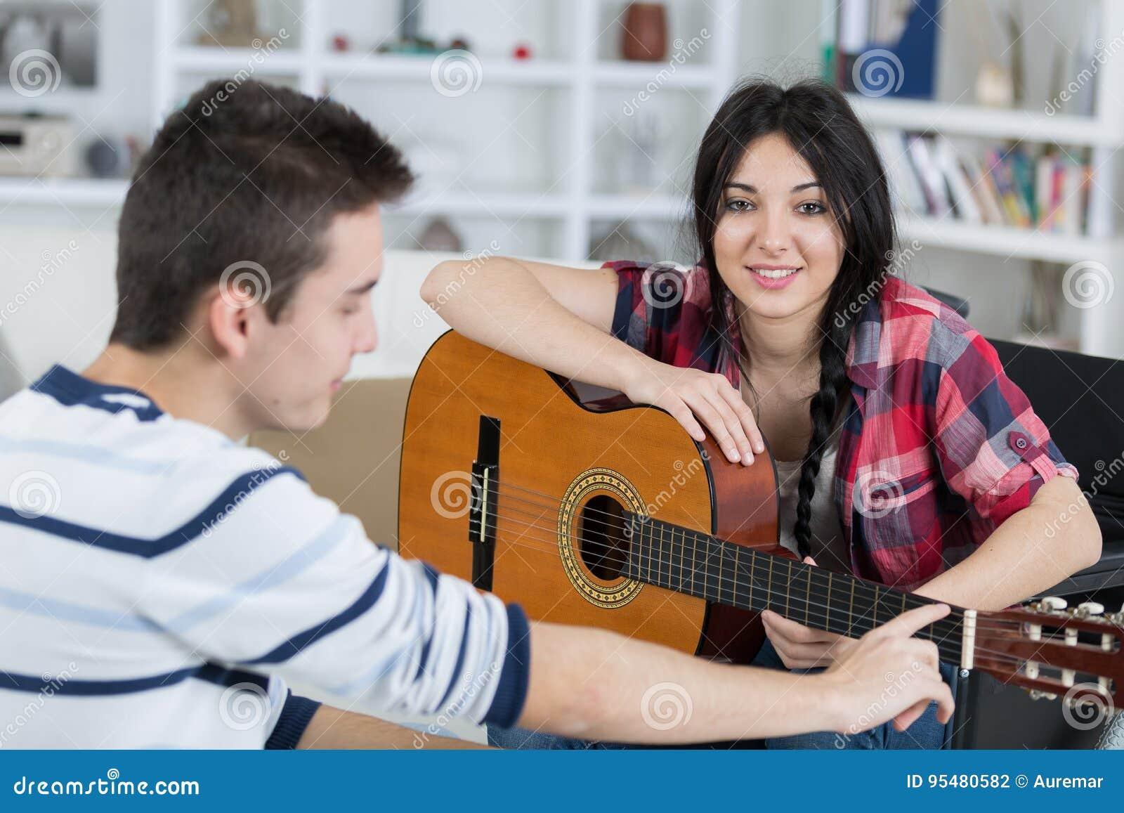 Młody człowiek uczy dziewczyny bawić się gitarę indoors