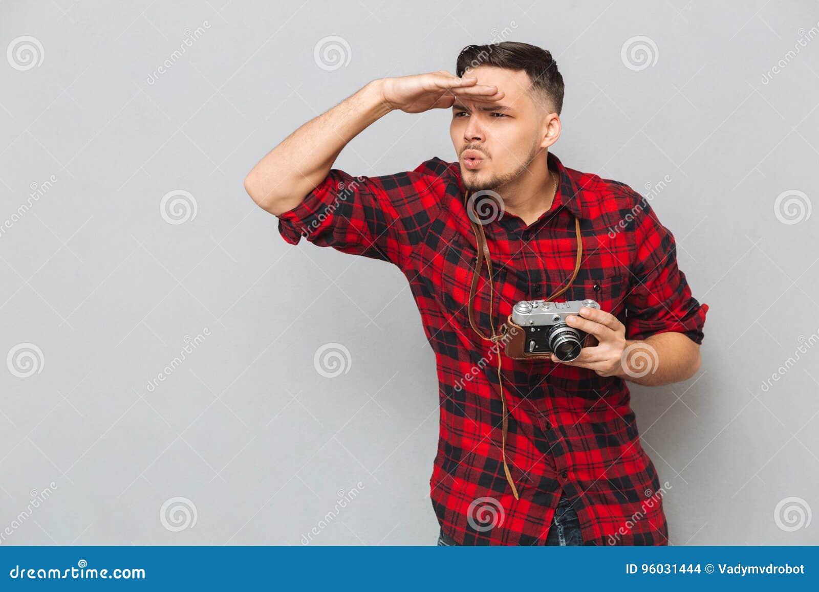 Młody człowiek w koszulowego mienia retro kamerze i patrzeć daleko od