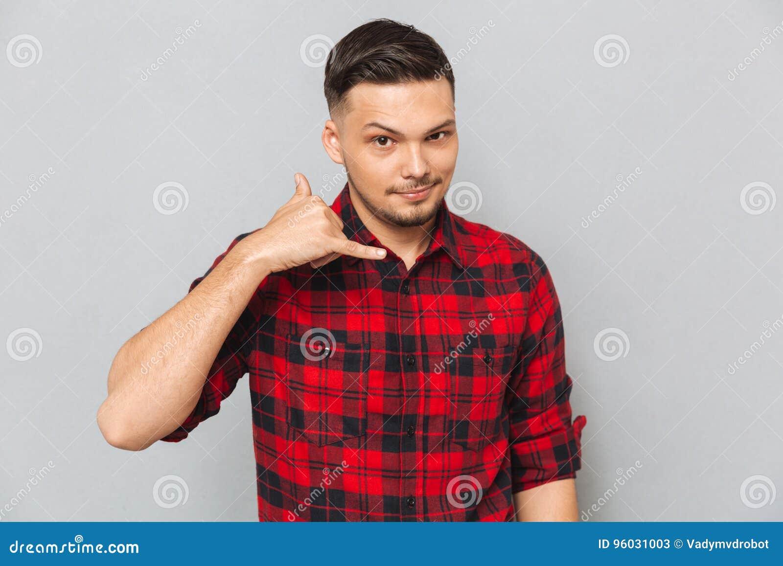 Młody człowiek w koszulowym seansu telefonu znaku
