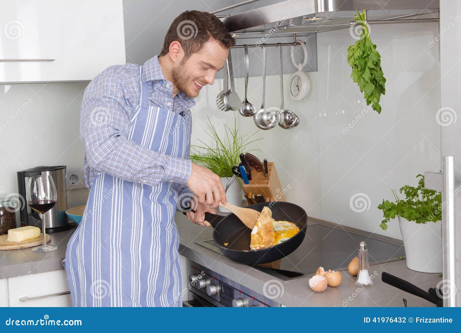 Młody człowiek w kuchenny kucharstwo smażących jajkach