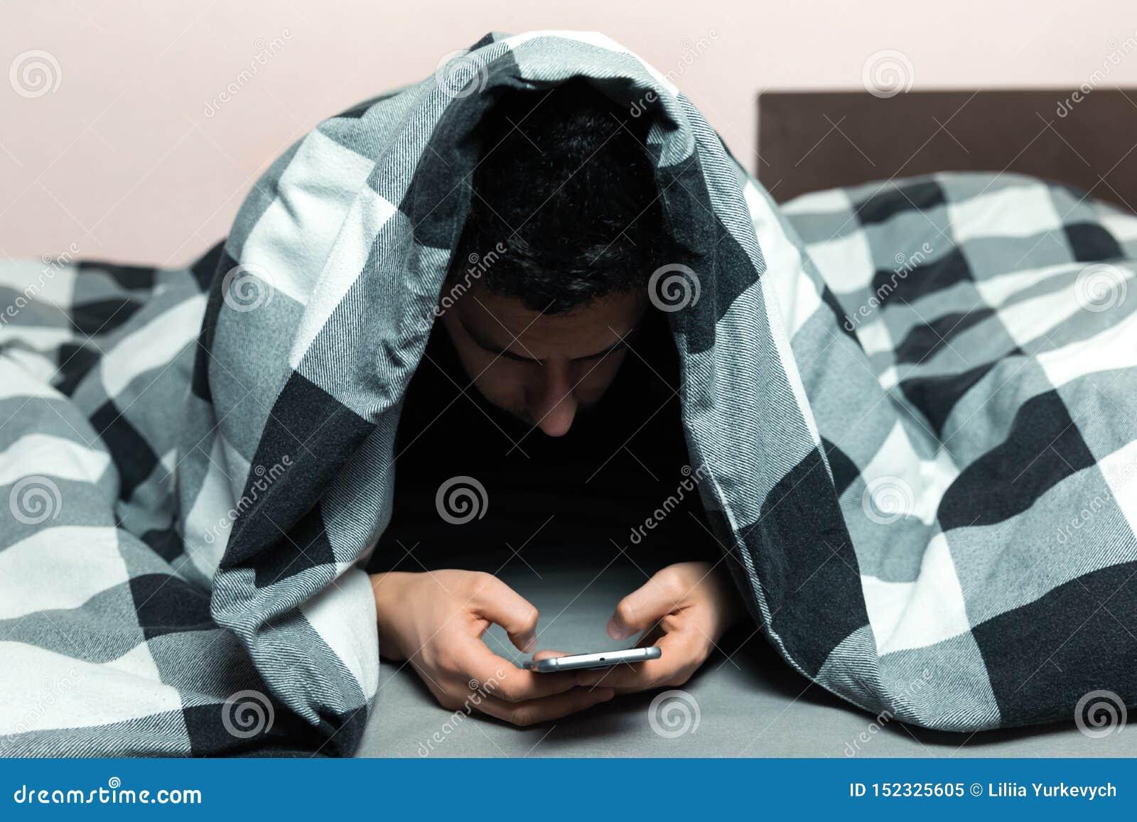 Młody człowiek w piżamach używać telefon komórkowego