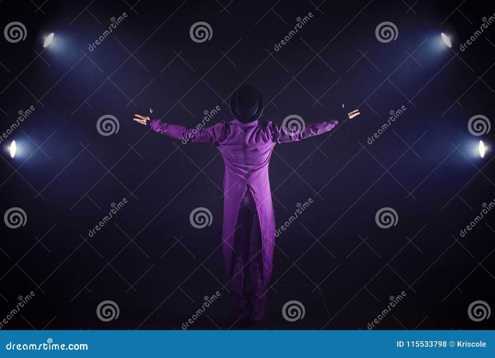 Młody człowiek w purpurach nadaje się pozycję na tle światło reflektorów Showman podesłania ręki, przedstawienie zaczynają