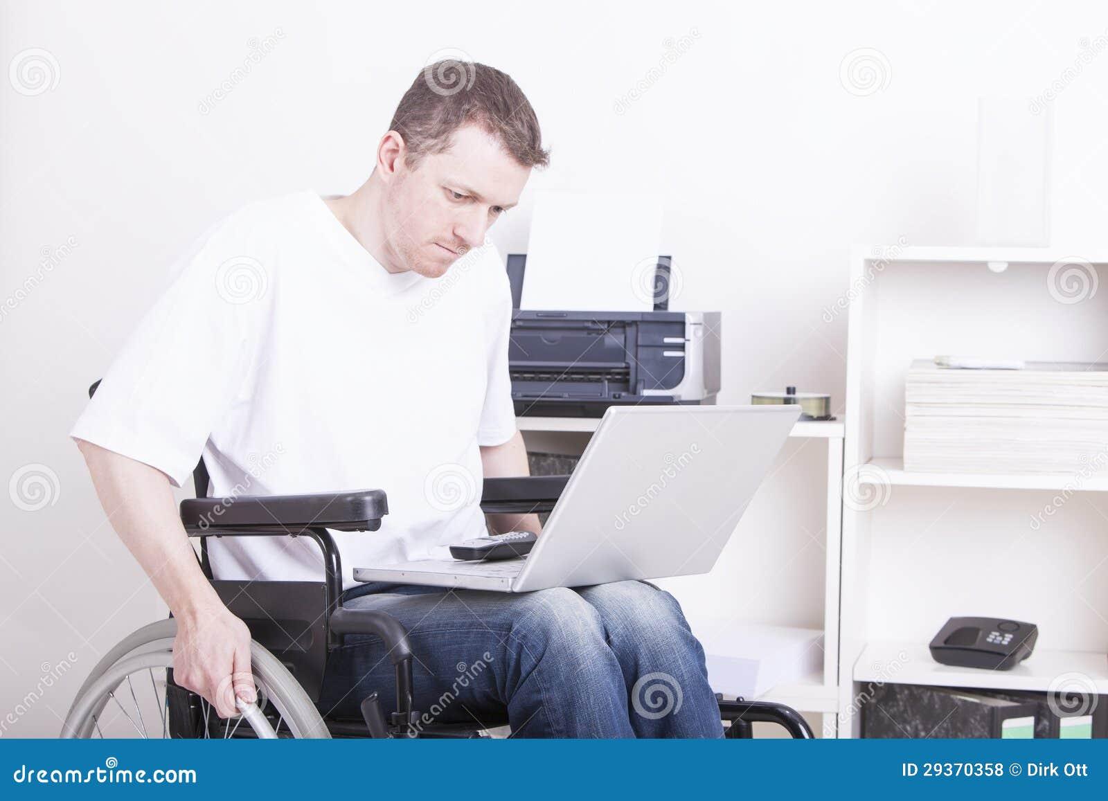 Młody człowiek w wózek inwalidzki biurze w domu
